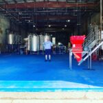 owner with beer tanks for brewing