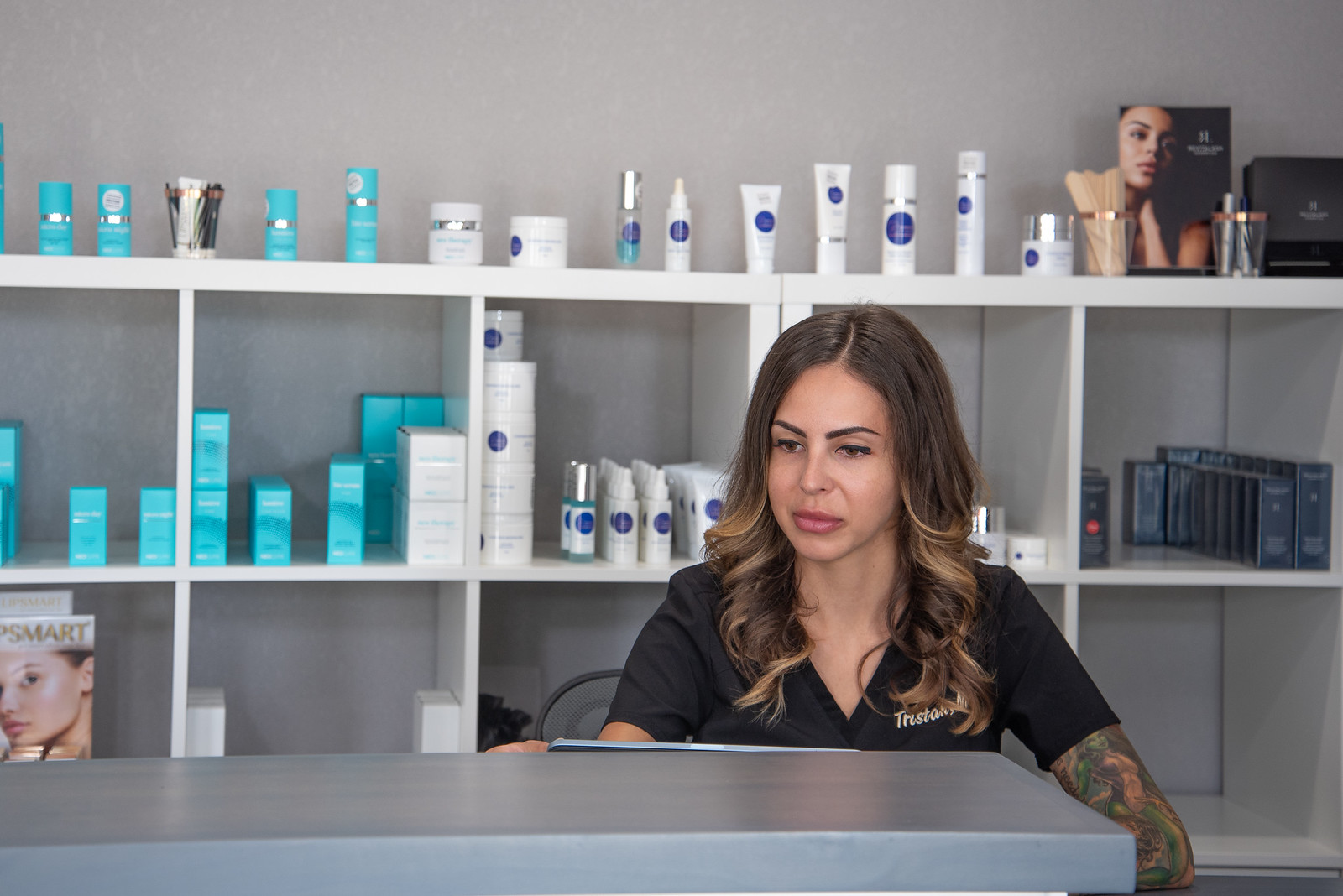 Tristah Romero-Kelly Owner of Renew Medical Aesthetics, she is sitting at her front desk in front of her products